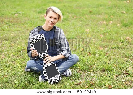 Teenager boy with hoverboard in park