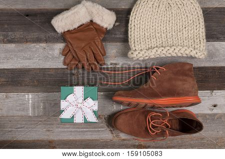 Winter clothes. Gifts for holidays and women's clothing on a wooden background.