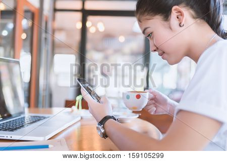 woman with beautiful smile reading good news on mobile phone during rest in coffee shop happy Caucasian female watching her photos on cell telephone while relaxing in cafe during free time