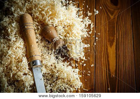 Woodworking tools. Chisel with sawdust on a wooden table poster