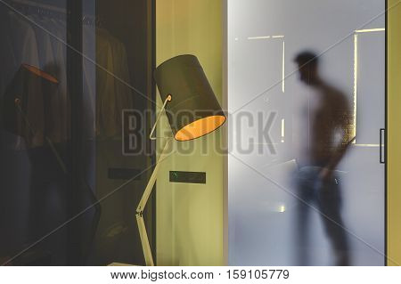 Man's silhouette who is behind the frosted glassy door in the glowing modern interior with yellow walls. In front of the door there is a luminous lamp with an orange lampshade and a glass partition.