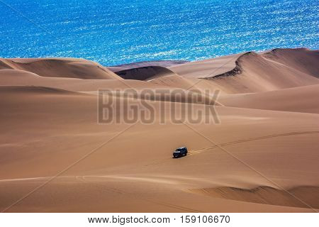 Sandwich Harbour - part of Namib-Naukluft National Park. Huge sand dunes moving on the Atlantic coast. Tourist trip by jeep