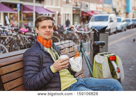 Tourist having take away breakfast in a street of Amsterdam