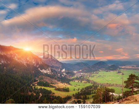 Beautiful Panoramic Landscape With Alpine Mountains And Neuschwanstein Castle