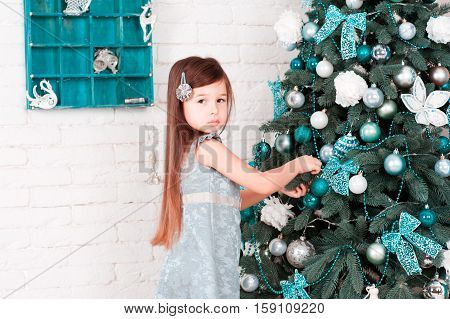 Baby girl 4-5 year old decorating christmas tree in room. Looking at camera. Celebration.