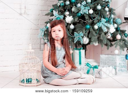 Cute kid girl 4-5 year old sitting with presents under christmas tree in room. Looking at camera. Childhood. Celebration. Merry christmas. Happy new year.
