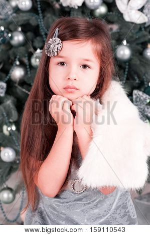 Baby girl 4-5 year old posing in room over christmas tree with decorations. Looking at camera. Merry christmas. Wearing stylish dress and fur jacket. Happy holidays.