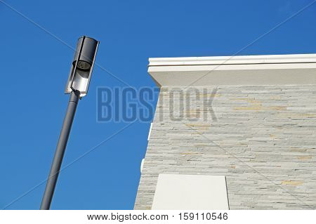 Closeup of a modern white metallic street lamppost with five lanterns against clear blue sky.