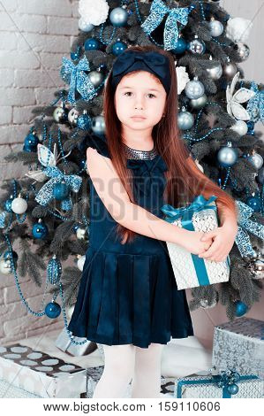Child girl 3-4 year old holding christmas present in room. Christmas tree. Looking at camera. Childhood. Holiday time. Merry christmas. Happy New Year.