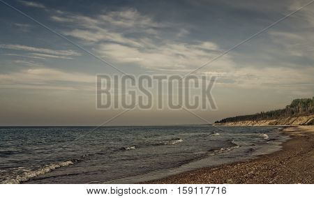 landscape with views of the Baltic Sea, on the banks of large and small stones and sand, small waves and endless horizon, blue sky and bright water, in distant cliff with pine trees, preset processed