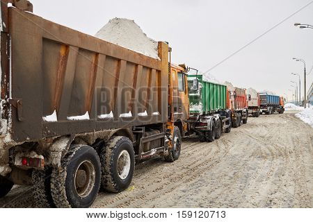 Trucks filled with snow stand on the road in winter.