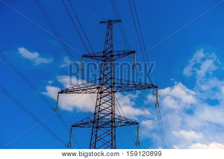 Pylon and transmission power line in summer at sunset