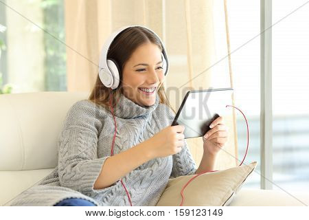 Girl wearing sweater listening music on line with a tablet sitting on a sofa in the living room at home in winter
