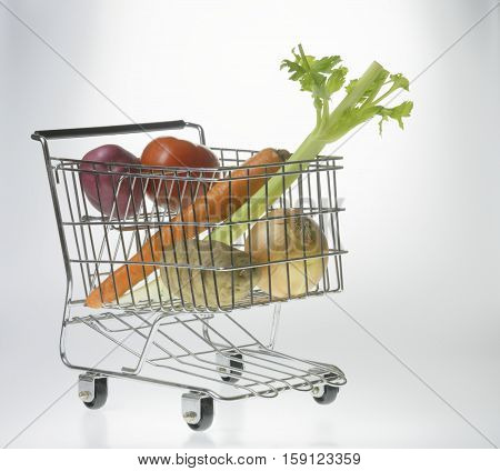 mini shopping cart as a vegetable basket or grocery cart holding tomato onion celery carrot and potatoes in front of a gradient white background with reflection viewed from front-right