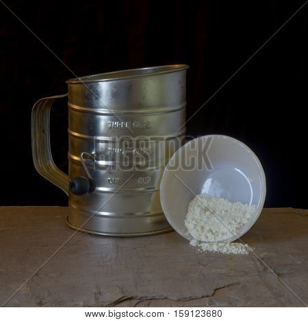 sifter and small upended bowl spilling flour on gray slate in front of black background