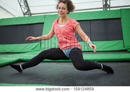 Young woman jumps on trampoline attraction in sitting position.