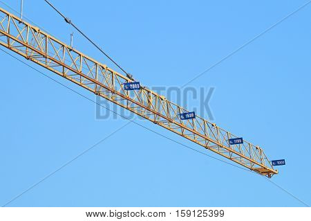 Construction industry tower crane against clear blue sky. Heavy metal frame structure showing counterweight and counterjib. Room for text, copy space.