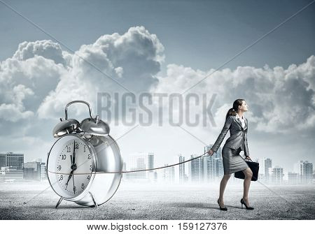 Elegant businesswoman with suitcase holding alarm clock on lead