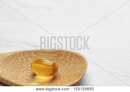 Wooden spoon with cod liver oil pill, closeup