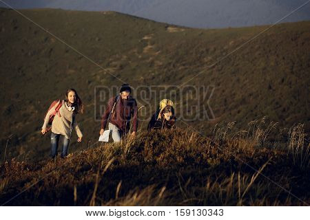 handsome bearded man in checkered shirt with pretty young cute girls or women smiling and walking with map on mountain top on sunny natural outdoor