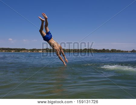 A man in swimming trunks jumping into a beautiful lake