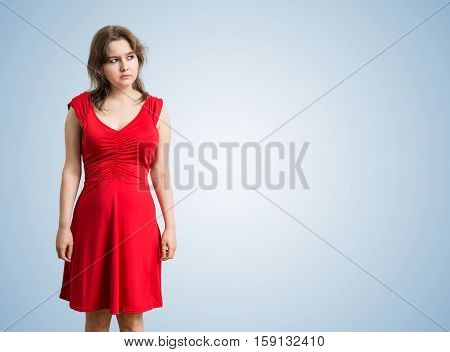 Young Thoughtful And Sad Woman Is Thinking On Blue Background.