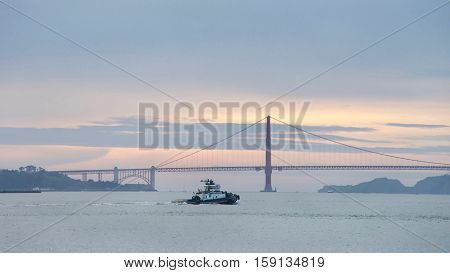 San Francisco CA - November 27 2016: Tugboat Z-THREE in the San Francisco Bay heading towards the Golden Gate Bridge sun setting in the background.