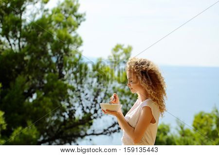 Pretty cute woman or sexy girl with curly blond hair stands with plate and spoon of morning breakfast eating food on balcony on summer day on natural background