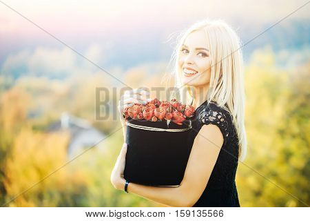 Pretty cute girl or beautiful blond woman in sexy black dress with red rose flowers in box outdoor on natural background