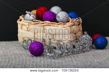 Wattled basket with Christmas decorations. Multi-colored spheres and brilliant tinsel. Close up small depth of sharpness