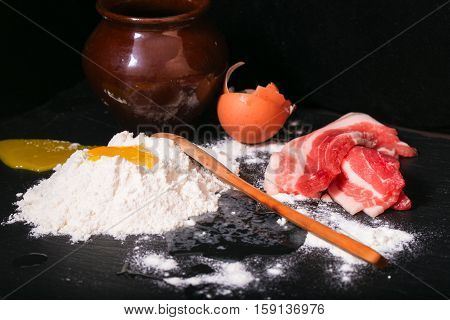 Crude products on a kitchen table. Crude bacon the broken egg and flour. On a background a clay ceramic pot on a flour hill a wooden spoon. Products against a dark background