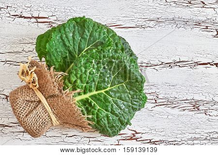 Raw organic savoy cabbage leaves on white rustic wooden background. Top view with copy space
