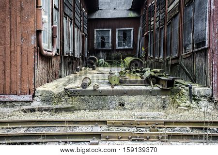 old wooden railroad building with assorted hardware and wheels next to tracks