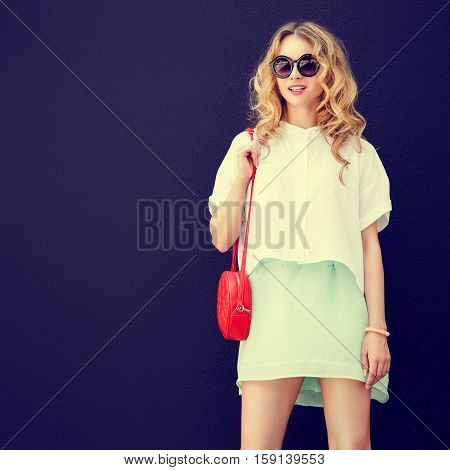 Stylish Girl in Sunglasses at the Dark Textured Wall Background. Urban Fashion Woman Concept in Summer. Trendy Street Style. Toned and Filtered Square Photo with Copy Space.