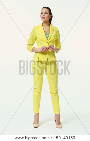 business woman with straight hair style in office yellow pant suit skirt suit high heel shoes going full body length isolated on white