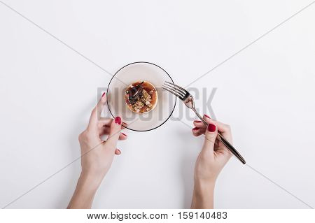 Female Hands With Red Manicure Holding A Cake On A Saucer And Fork