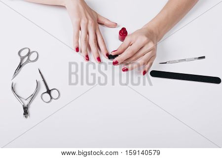 Female Hand Applied Red Lacquer On The Nails, The Top View