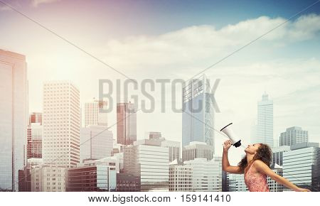 Young woman in dress making announcement in megaphone
