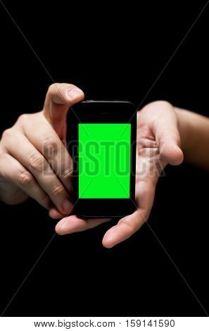 Hands Holding Smartphone showing Empty Green Screen (on black background with very shallow depth of field)