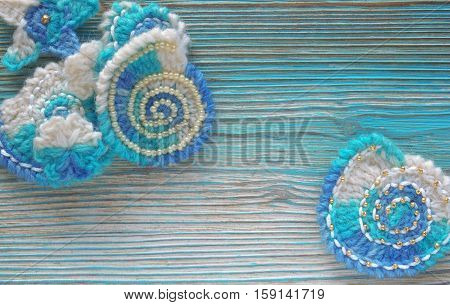 Marine background with cotton lace crochet elements: stars shells and flowers made of Multi color wool soft yarn