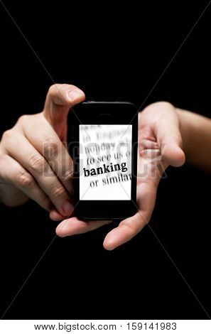 Hands Holding Smartphone showing the Word Banking printed concept of phone banking (on black background with very shallow depth of field)