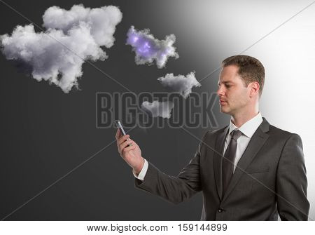 Handsome young man holding smartphone with abstract clouds. Cloud sync concept