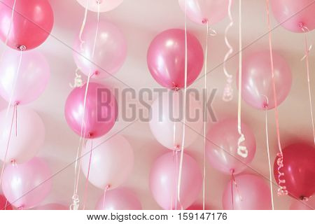 pink hydrogen balloons with ribbon at ceiling