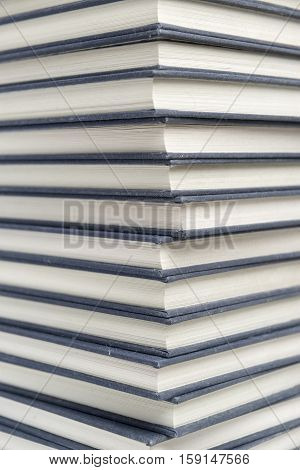 Stack of dusty hardcover books detail closeup