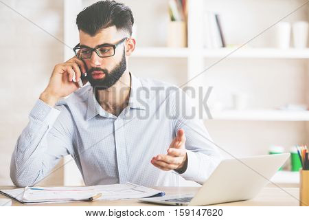 Attractive young businessman sitting at his office desk with laptop supplies other items and talking on mobile phone. Communication concept
