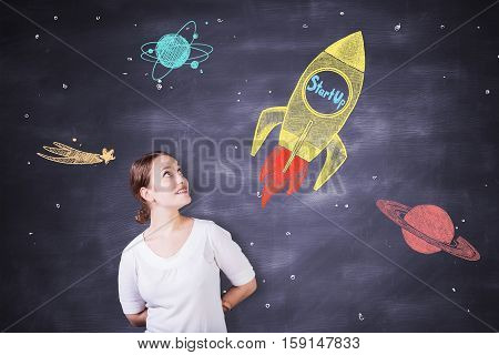 Cheerful caucasian female on chalkboard background with creative rocket ship sketch. Startup concept