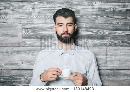 Close up portrait of handsome bearded young guy with coffee cup on wooden background
