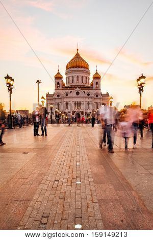 Patriarchal bridge with people blurring. Christ the Savior Cathedral at sunset