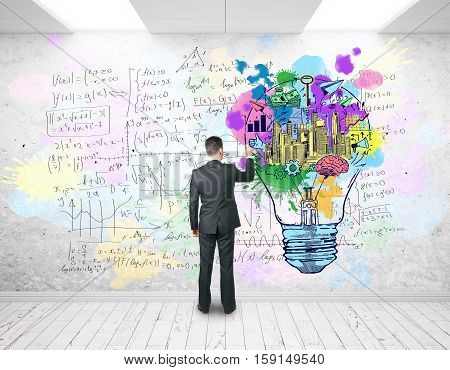 Back view of businessman drawing lamp and mathematical formulas on wall. Business and education concet