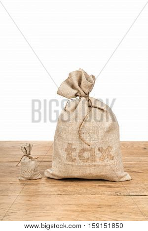 Small bag with the word profit and a big bag of tax lying on wooden table isolated on white background
